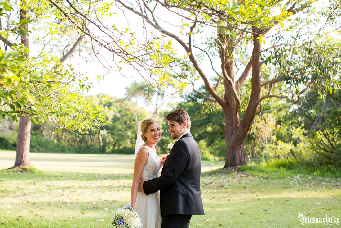 A smiling bride and groom embrace under some trees
