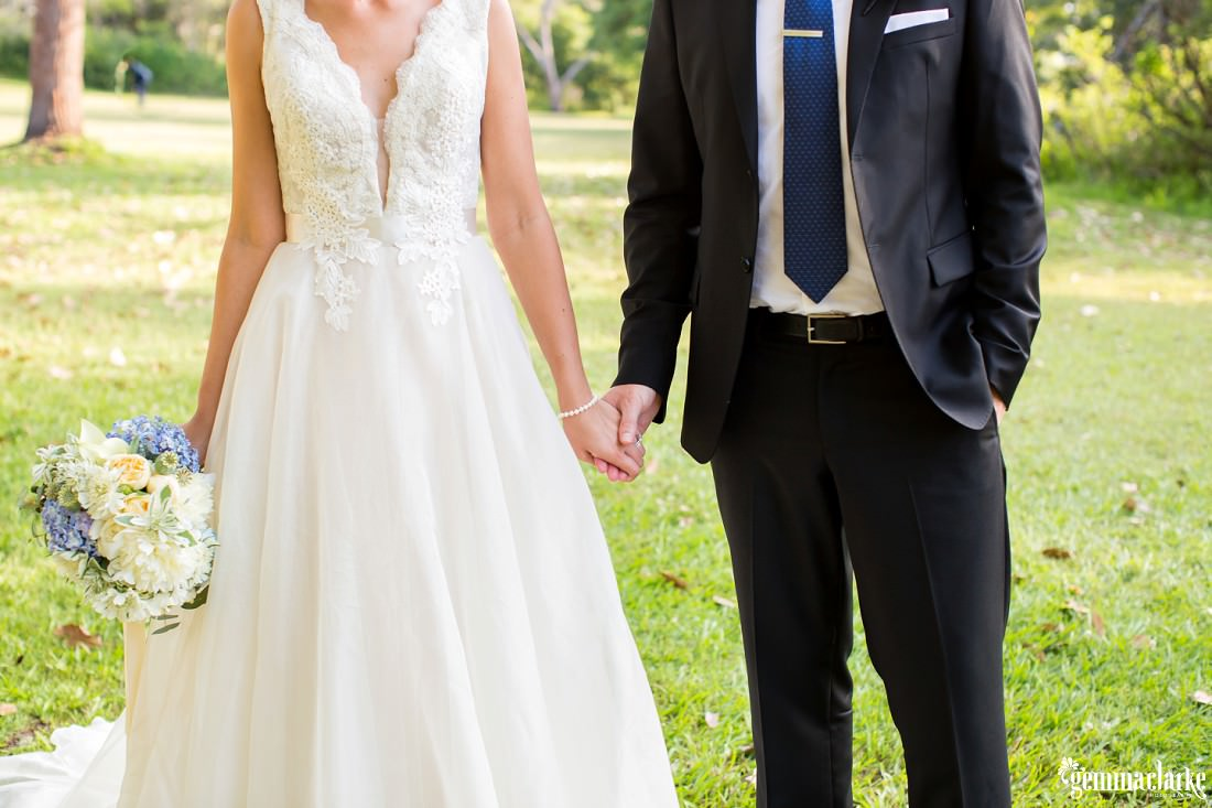 A closeup of a bride and groom holding hands