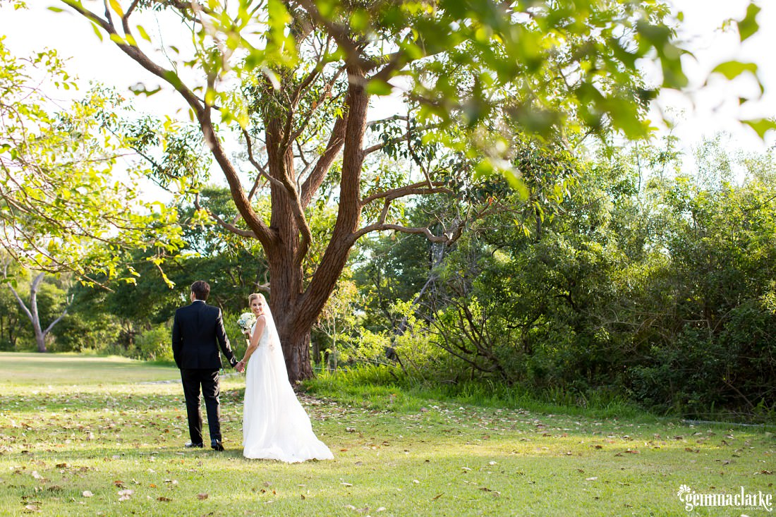 A bride and groom holding hands and walking, the bride looking back over he shoulder