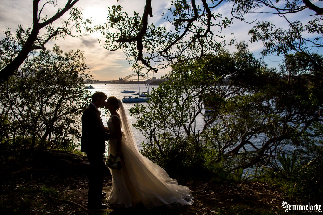 A silhouette of a bride and groom kissing under trees with the Sydney Harbour Bridge in the background