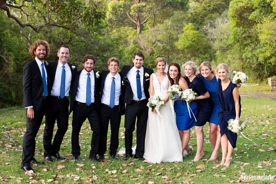 A bridal party smiling and posing with their arms around each others shoulders