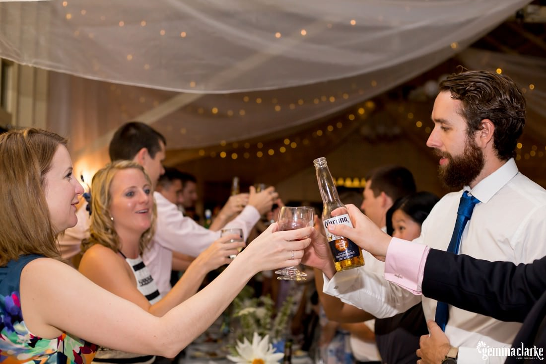 Wedding guests clinking their glasses and beer bottles together