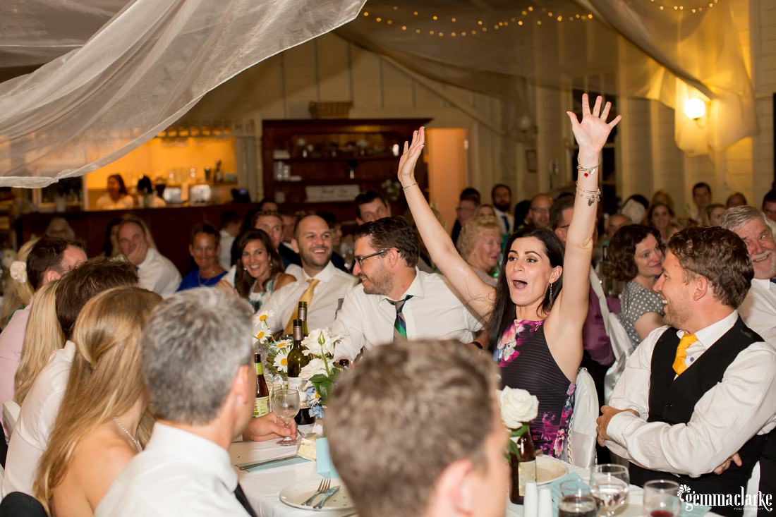 A wedding guest with her hands in the air as those around her smile