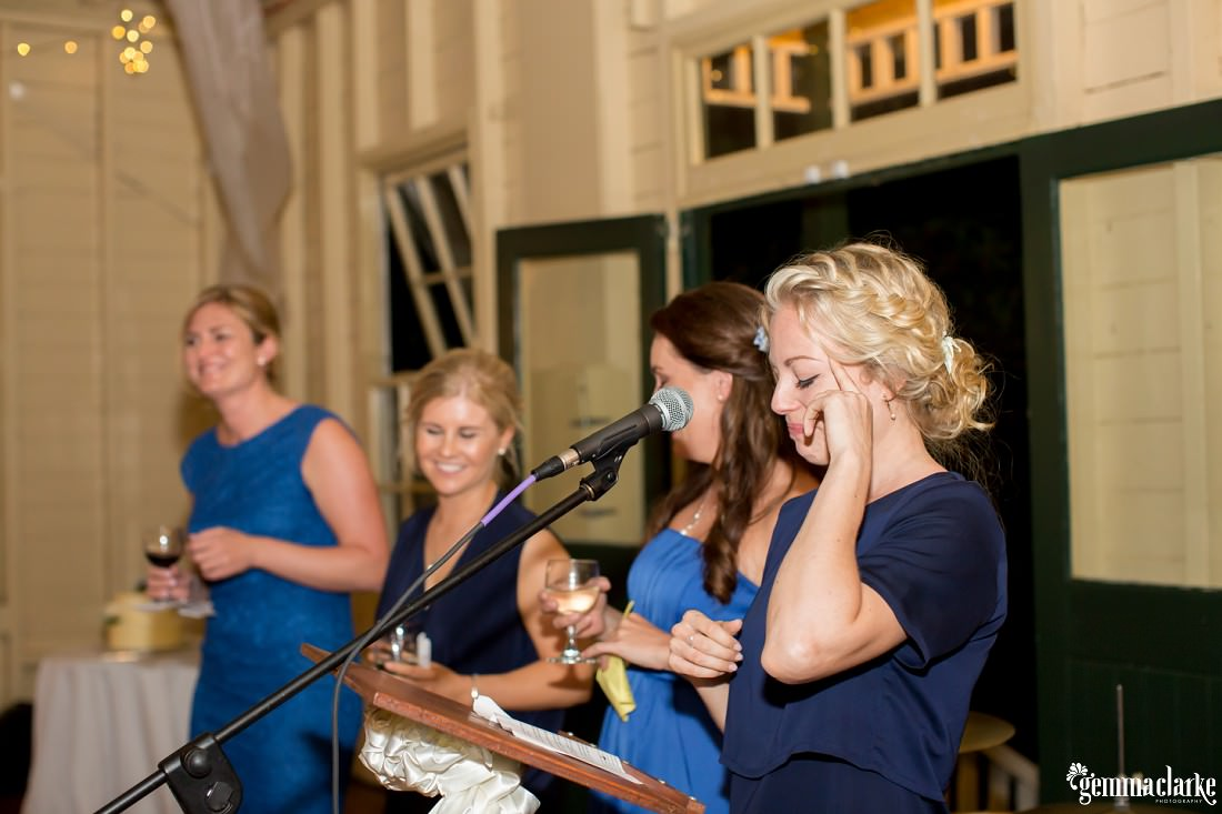 Bridesmaids deliver a speech at a wedding reception