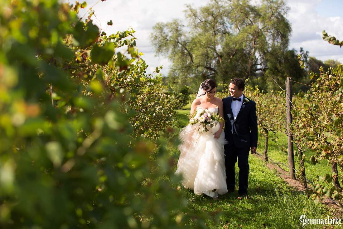 A bride and groom walk together through a vineyard
