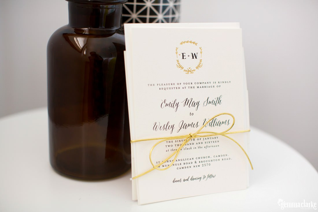 Wedding invitations wrapped in string standing against a bottle on a white table