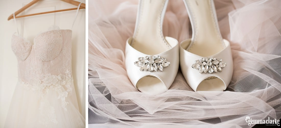 A white bridal gown hanging up and white bridal shoes