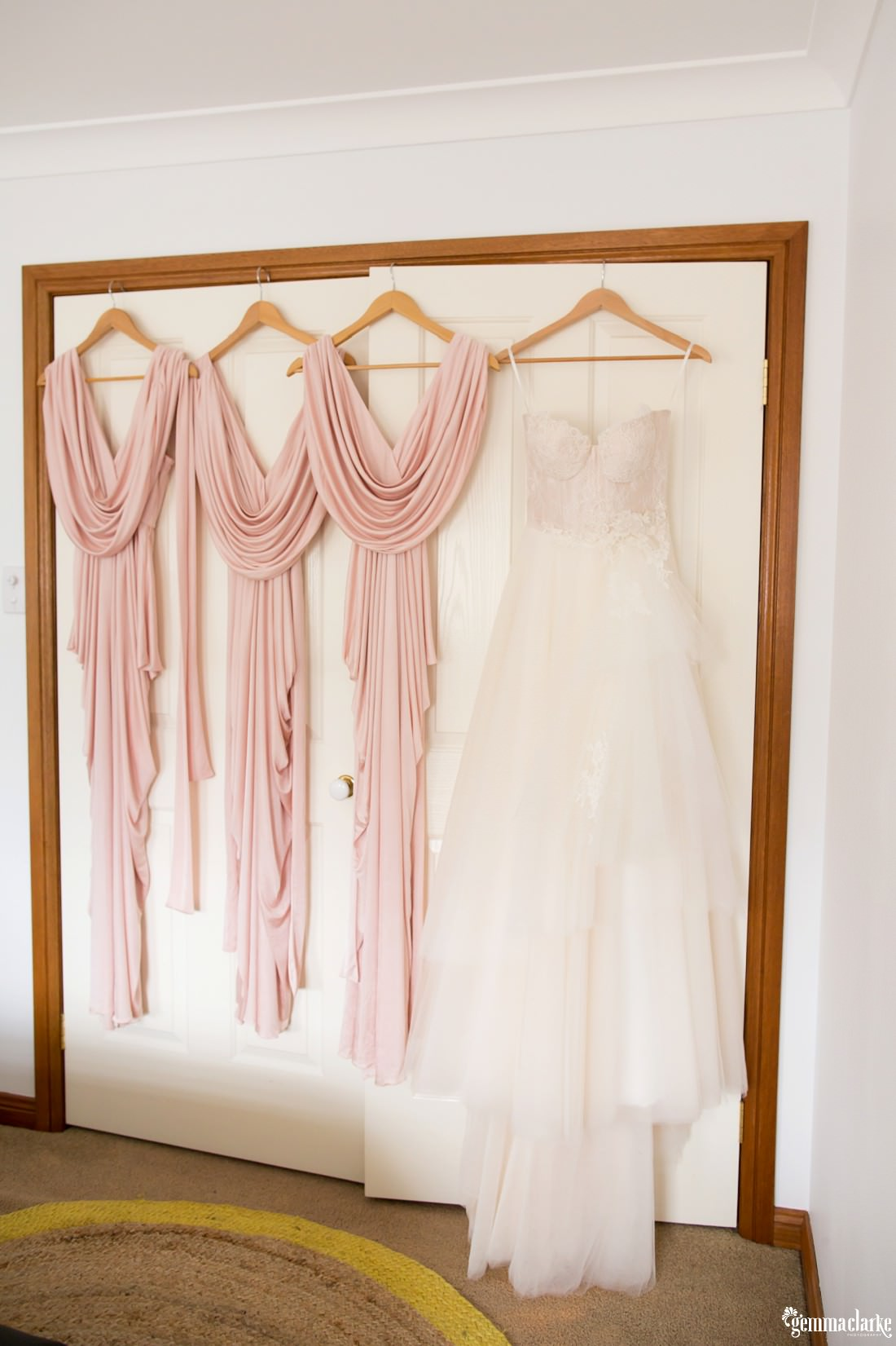 A white bridal gown and three blush pink bridesmaids dresses on hangers