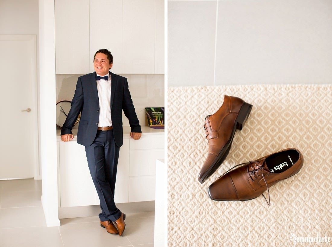 A smiling groom in a suit and bow tie leans against a counter in a kitchen, and a closeup of his shoes