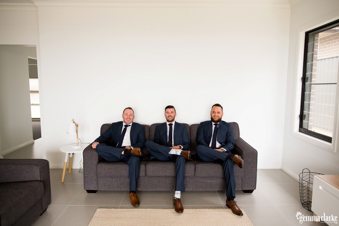 Three smiling groomsmen relaxing on a couch