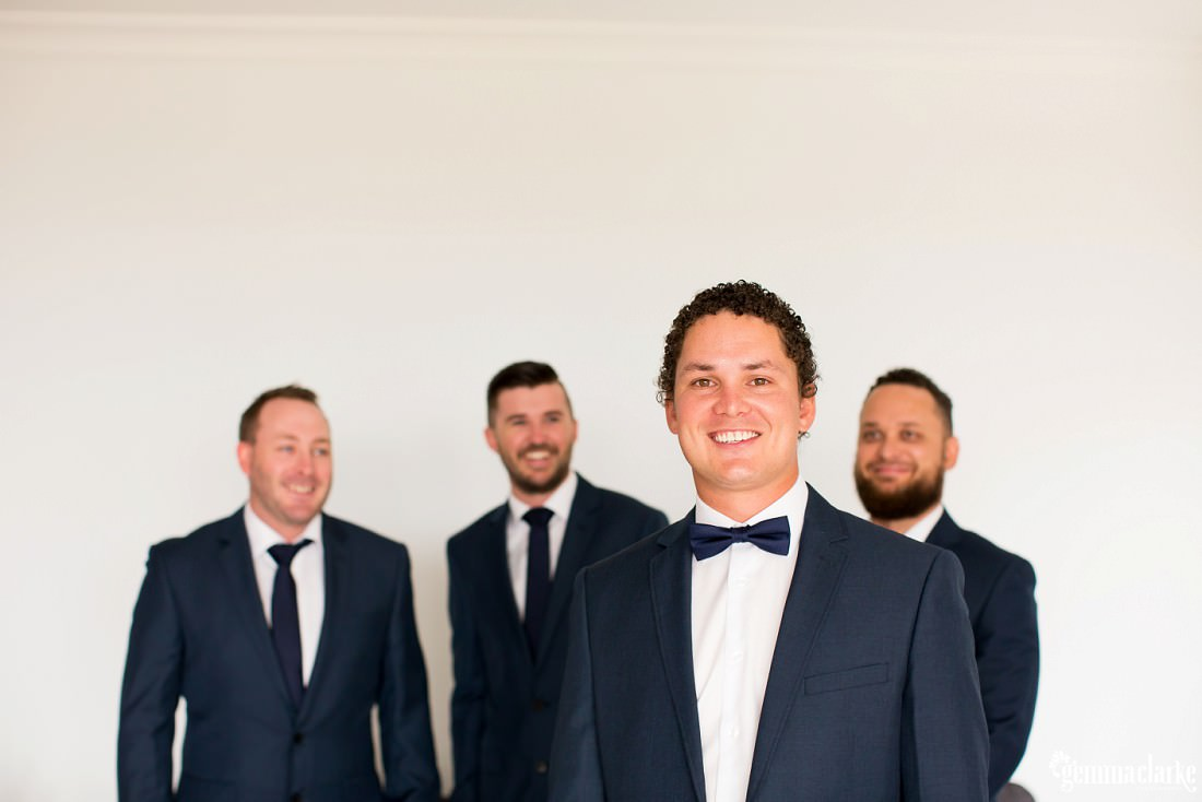A smiling groom with his three groomsmen looking at him from behind
