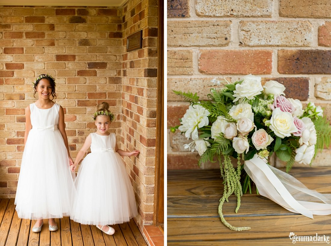 A flower girl and junior bridesmaid wearing white gowns and floral crowns, and a bouquet of light coloured flowers