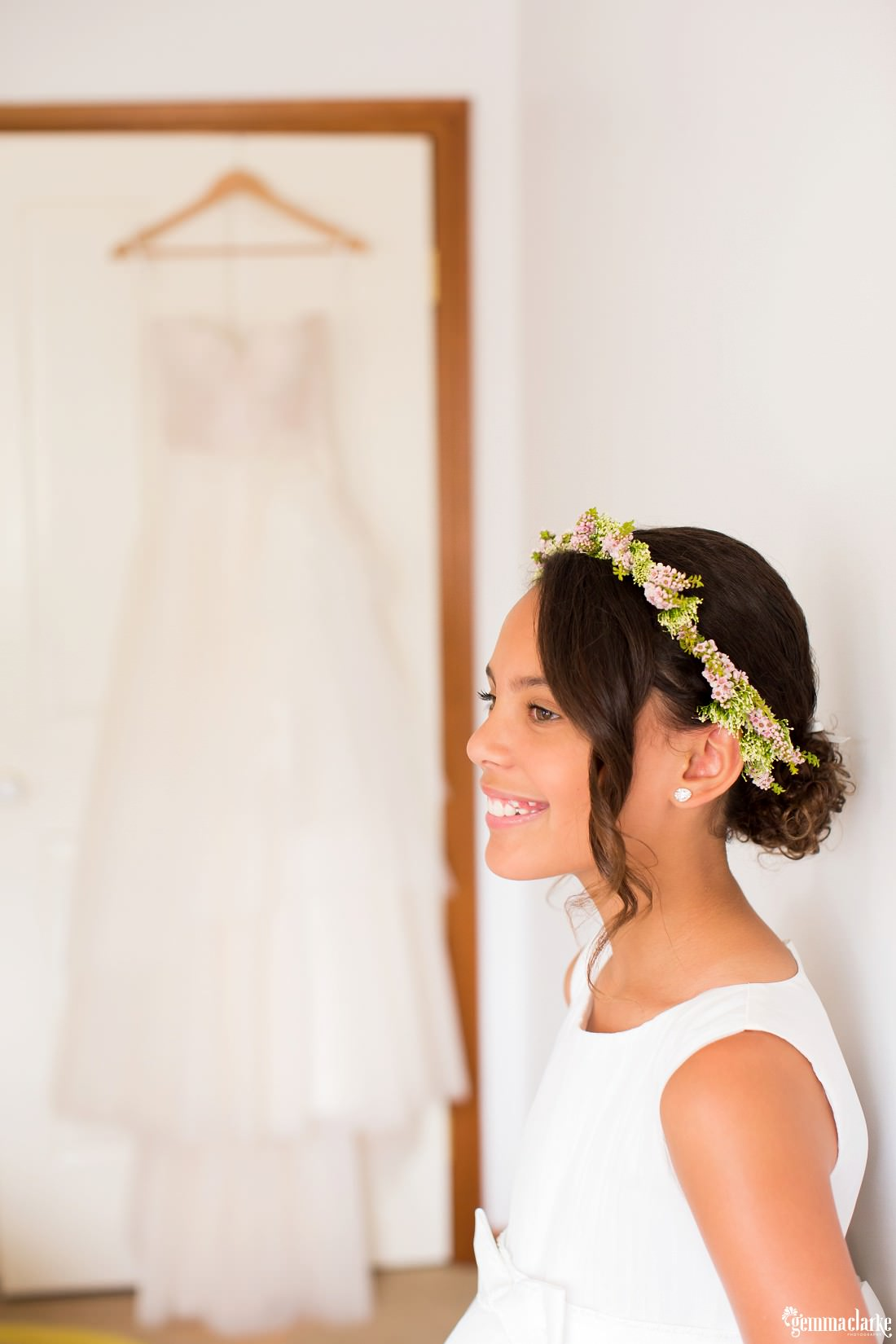 A smiling junior bridesmaid in white dress and floral crown