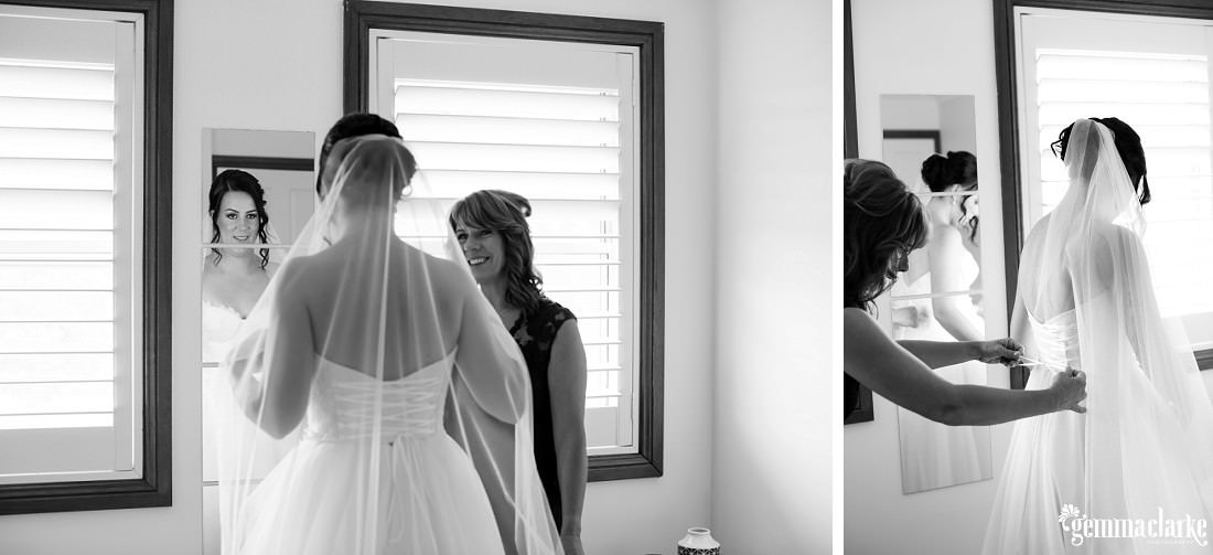 A bride checks her dress in the mirror and has some assistance tying up the back