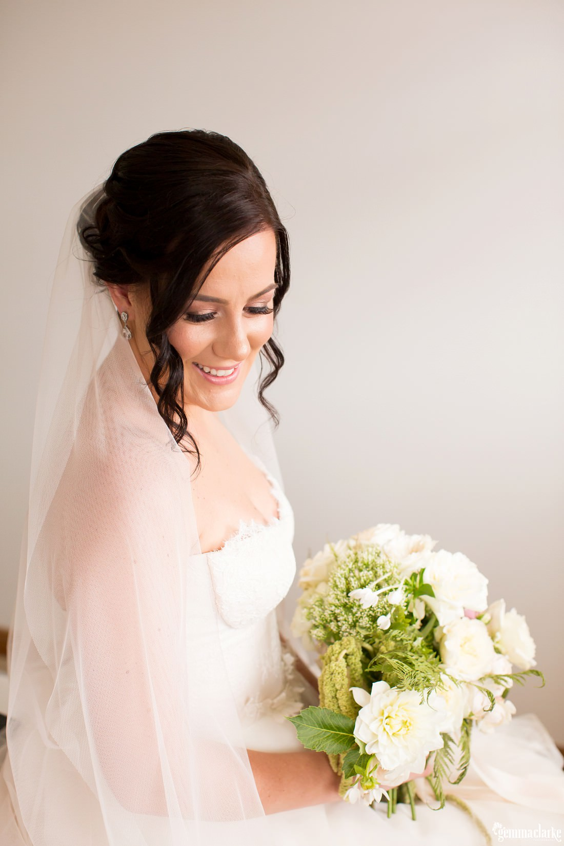 A smiling bride sitting and holding a bouquet of lightly coloured flowers