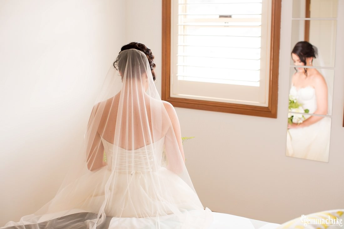 A shot of a bride from behind showing the detail of the back of her dress and her veil, and her reflection is seen in a mirror