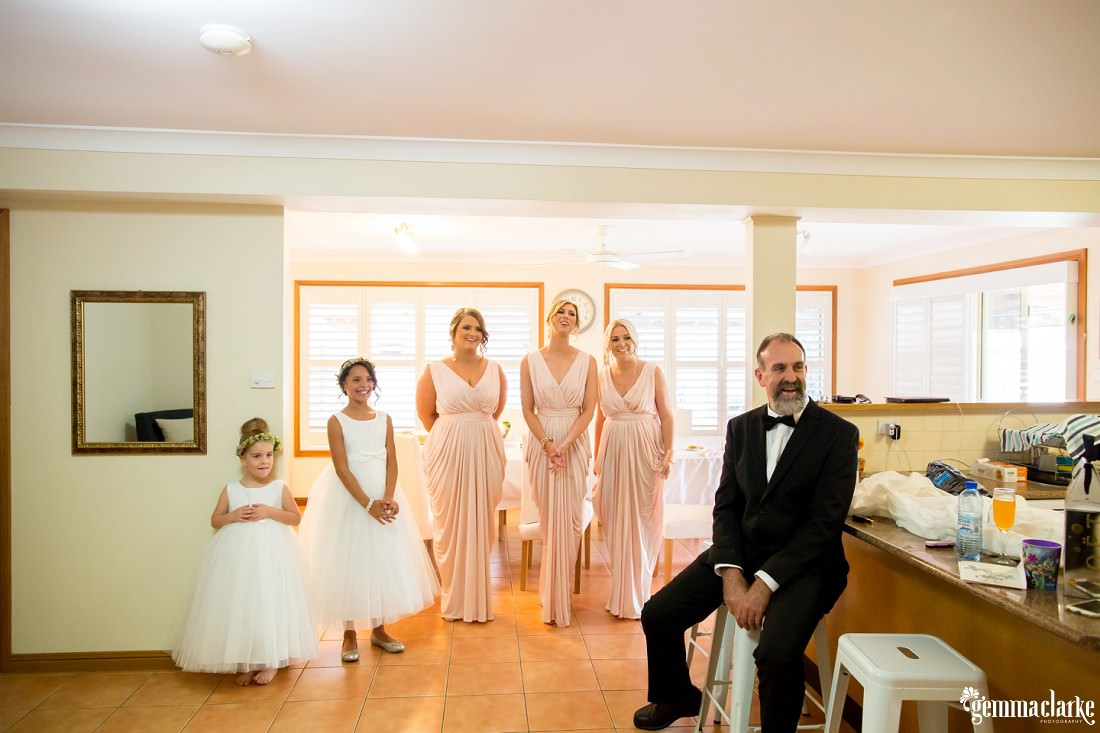 A bride's father, bridesmaids, junior bridesmaid and flower girl smile as they see her in her gown for the first time