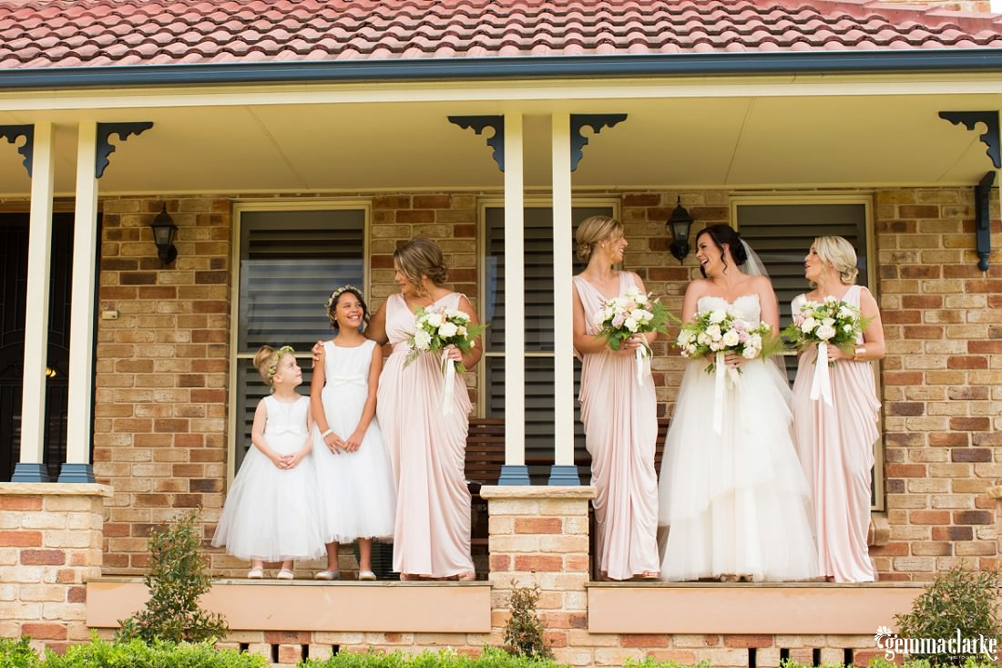 A bride and her bridesmaids and flower girl smile while standing on a verandah