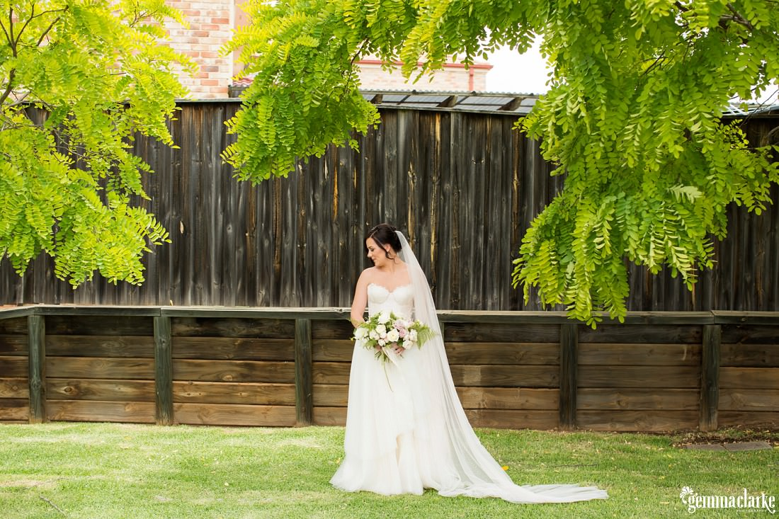 A bride holding her floral bouquet standing underneath a tree in front of a wooden fence