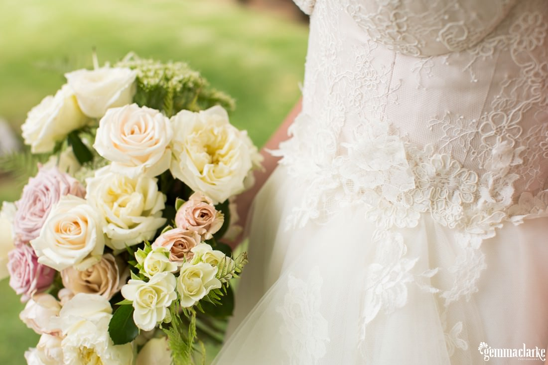 A closeup of the detail of a bridal gown and a lightly coloured floral bouquet
