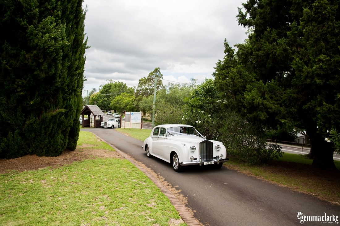 White wedding cars approaching a church