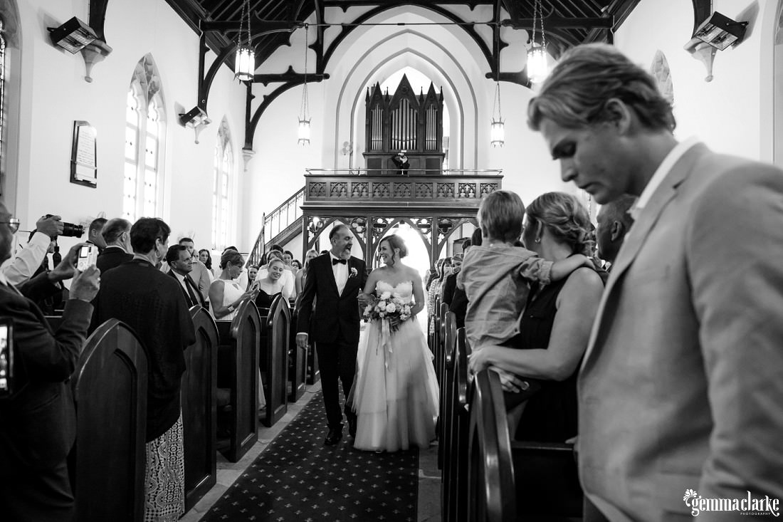 A bride and her father smile at each other as they walk together down the aisle of a church