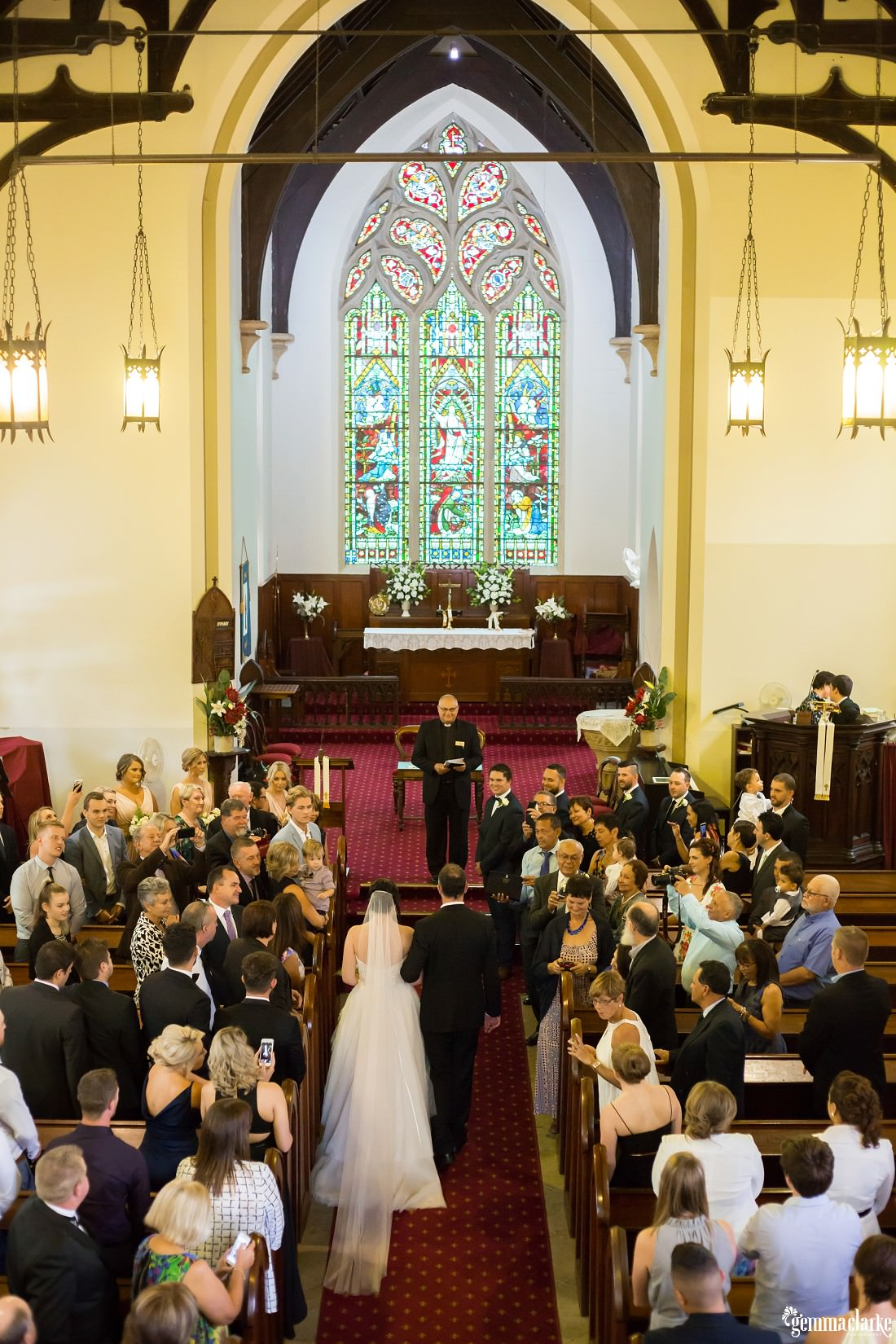 An overhead shot of a bride being walked down the aisle of a church by her father as her groom waits at the altar