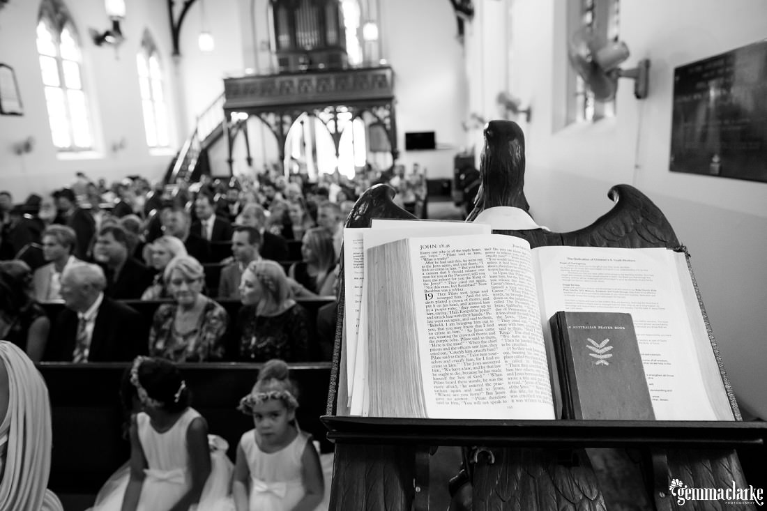A closeup of books on a lectern while wedding guests look on from church pews in the background