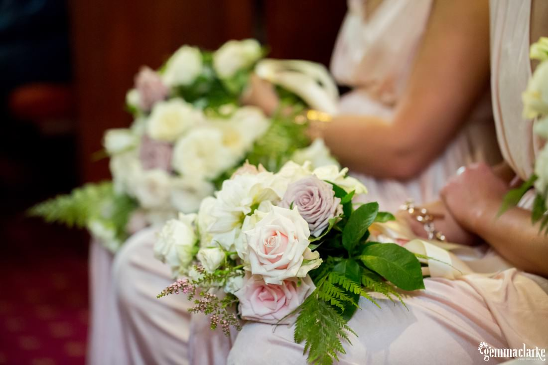 A floral bouquet on a bridesmaid's lap