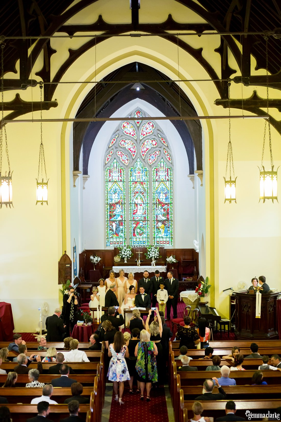 Wedding guests take photos of the bridal party in a church