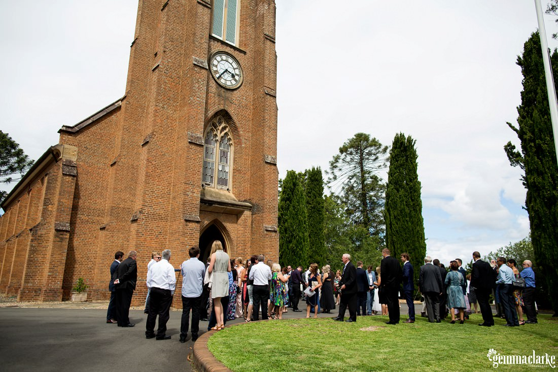 Wedding guests mingling outside a church