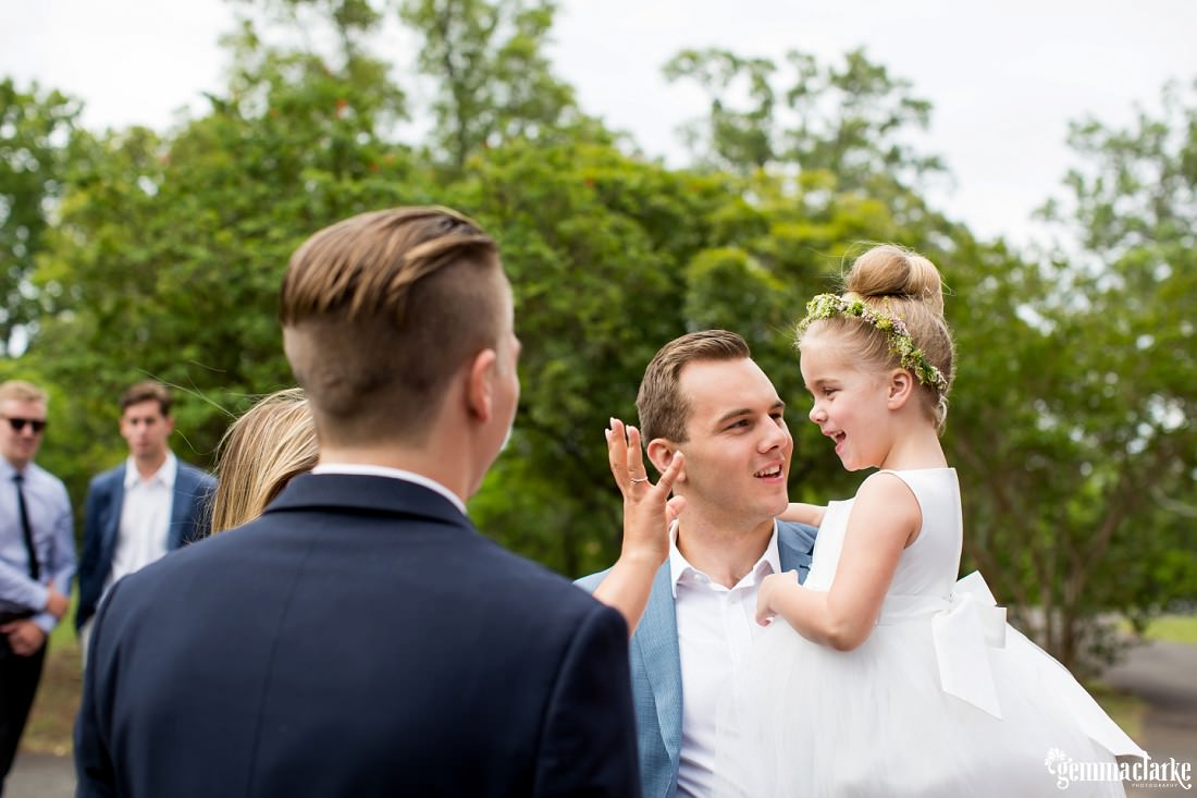 A flower girl with her father outside a church