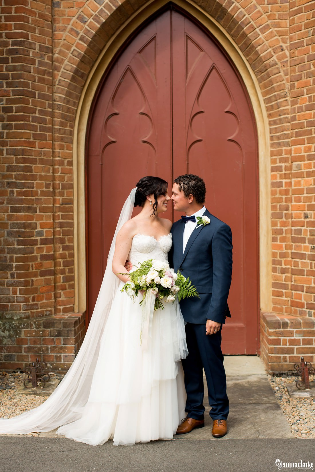 A bride and groom share an eskimo kiss in front of a church door