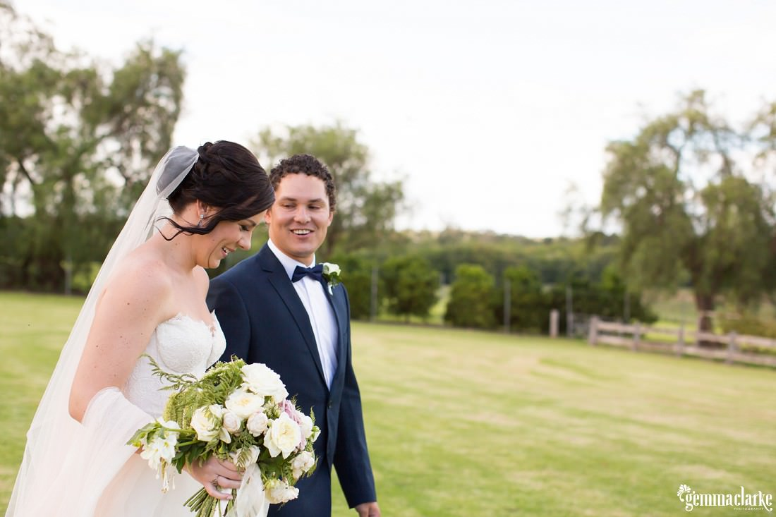 A groom looks lovingly at his bride as they walk across some grass