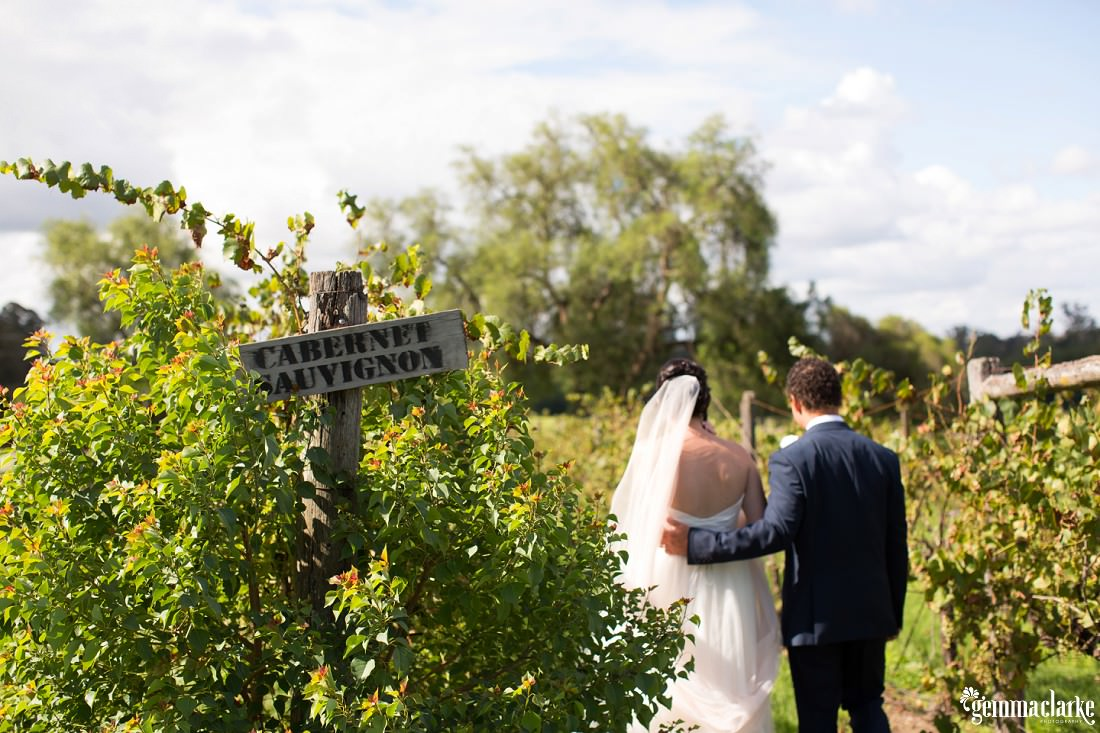 A groom walking with an arm around his bride through a vineyard