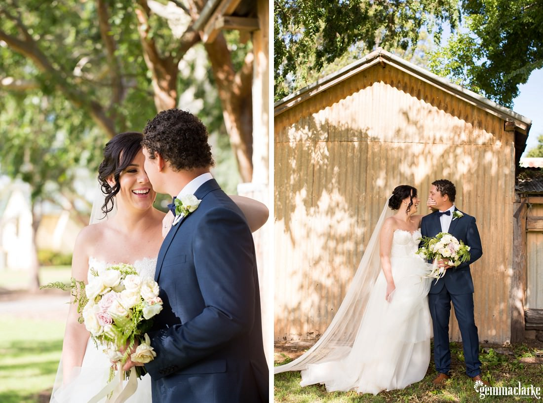 A smiling bride covers her groom's mouth with her hand as they stand in front of a corrugated shed