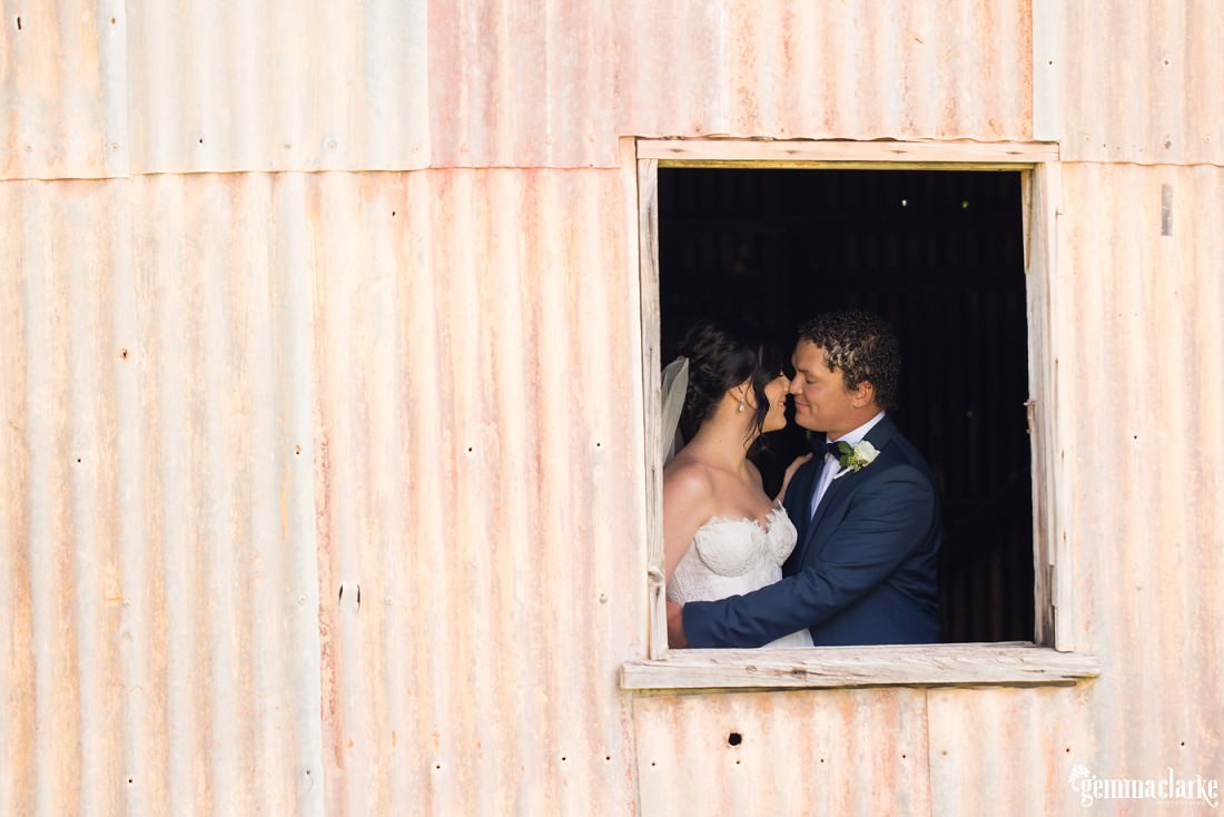 A bride and groom embracing and sharing an eskimo kiss as seen through a window in a corrugated shed