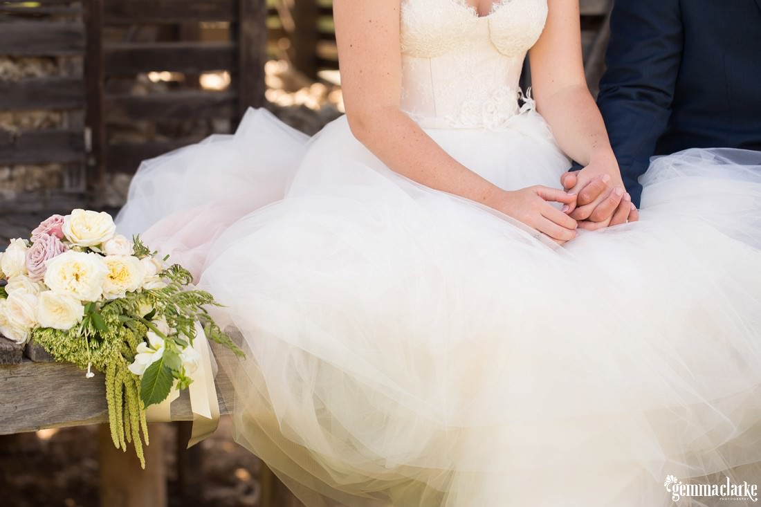 A bride and groom holding hands and sitting on a wooden bench