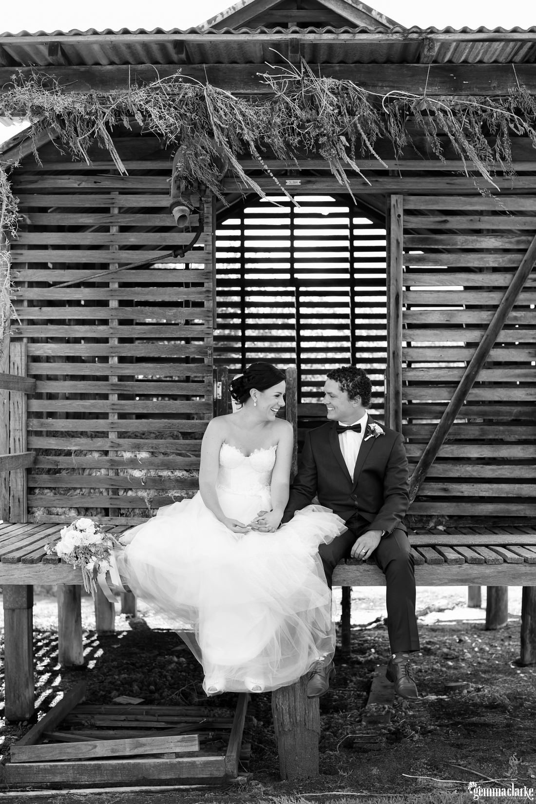 A bride and groom smile at each other and hold hands while sitting on the deck of a small wooden building