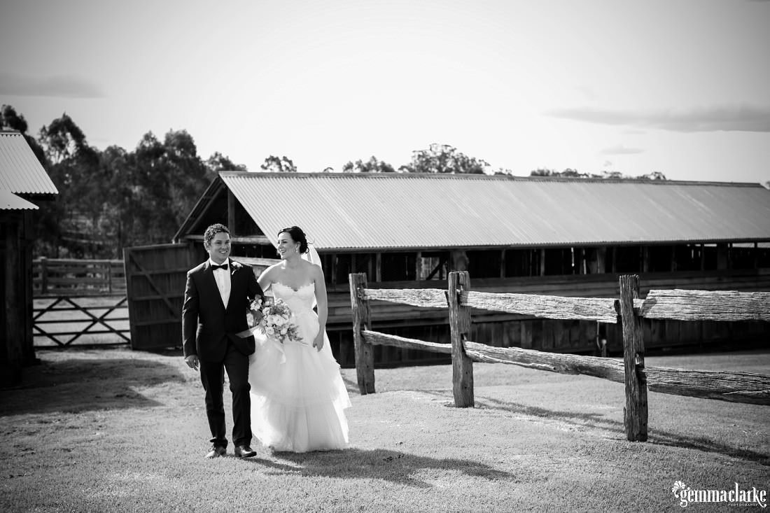 A bride and groom arm in arm walking away from wooden farm buildings