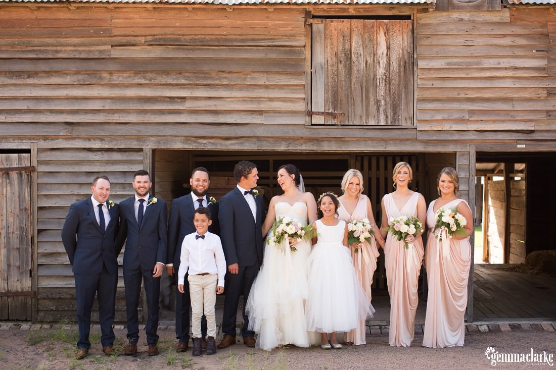 A smiling bridal party standing in front of a wooden farm building
