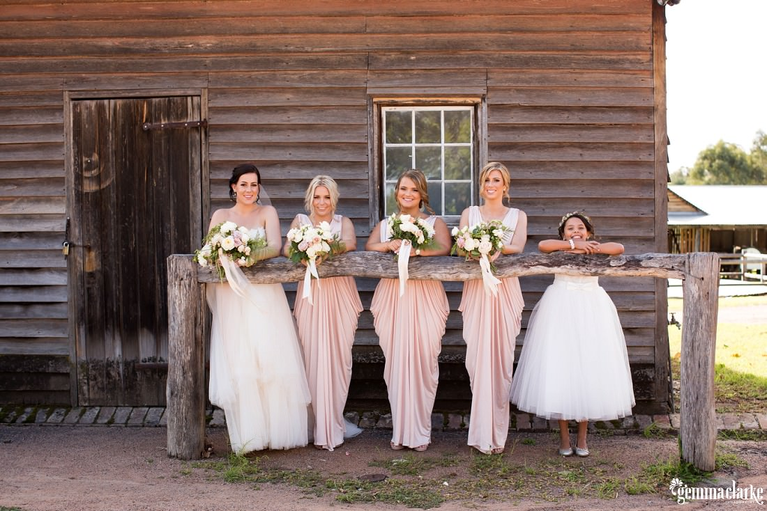 A bride and her bridesmaids leaning against a hitching rail