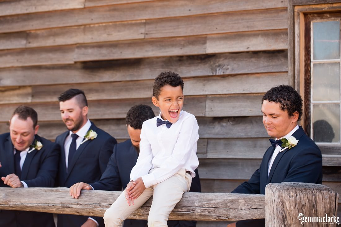 A page boy with a huge smile sitting on a hitching rail with groom and groomsmen in the background