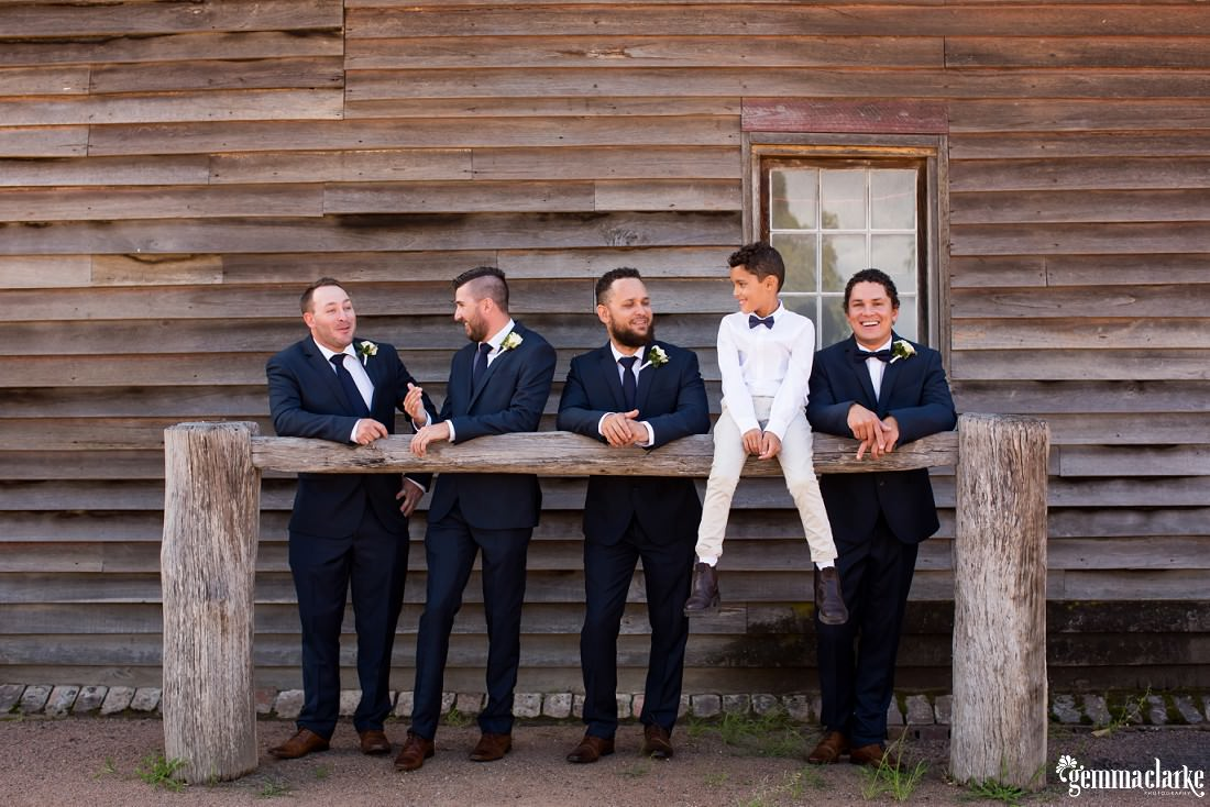 A page boy sits and groom and groomsmen lean on a hitching rail