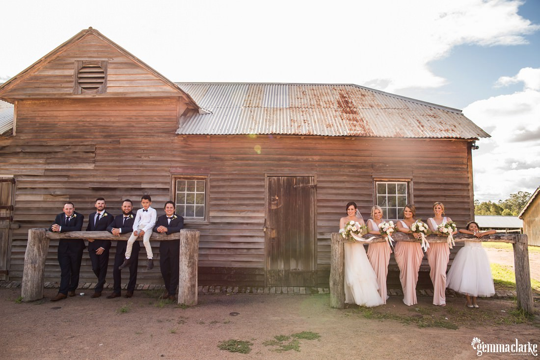 A wedding party leaning against two hitching rails in front of a wooden building