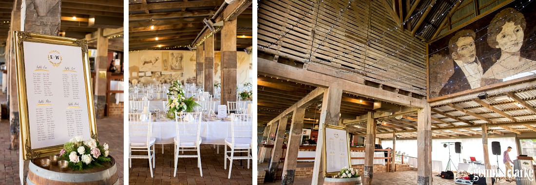 A sign with seating arrangements, and tables and chairs at a wedding reception in a large wooden farm building