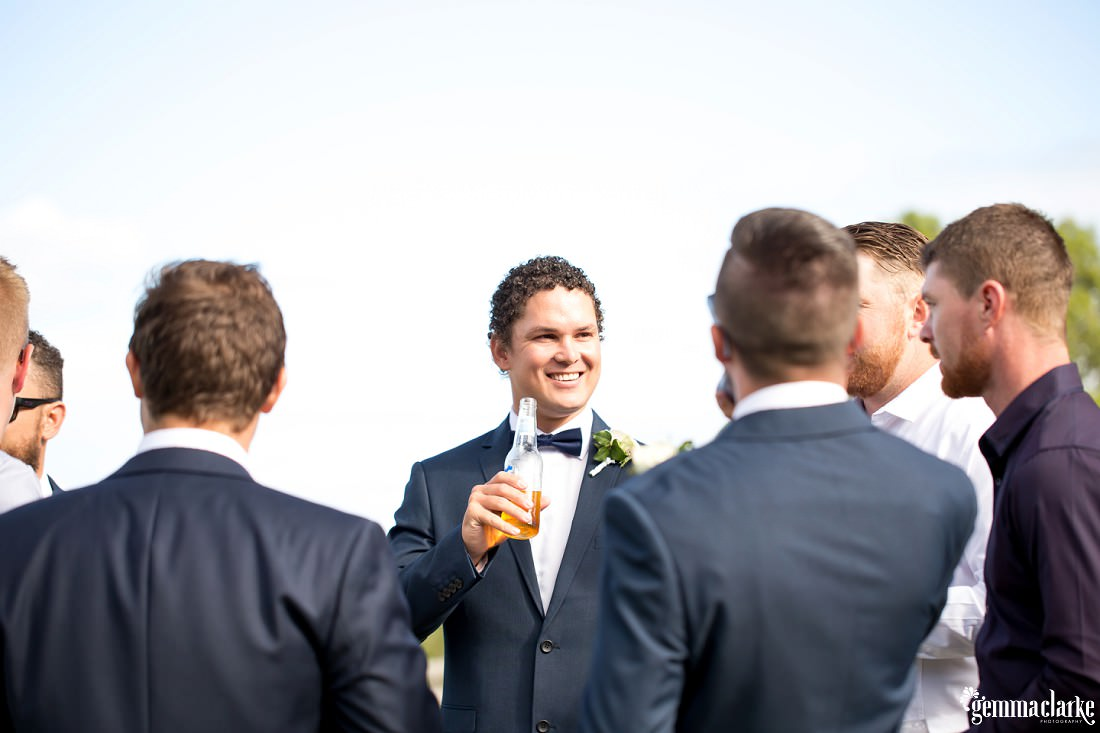 A groom drinks a beer and chats with wedding guests