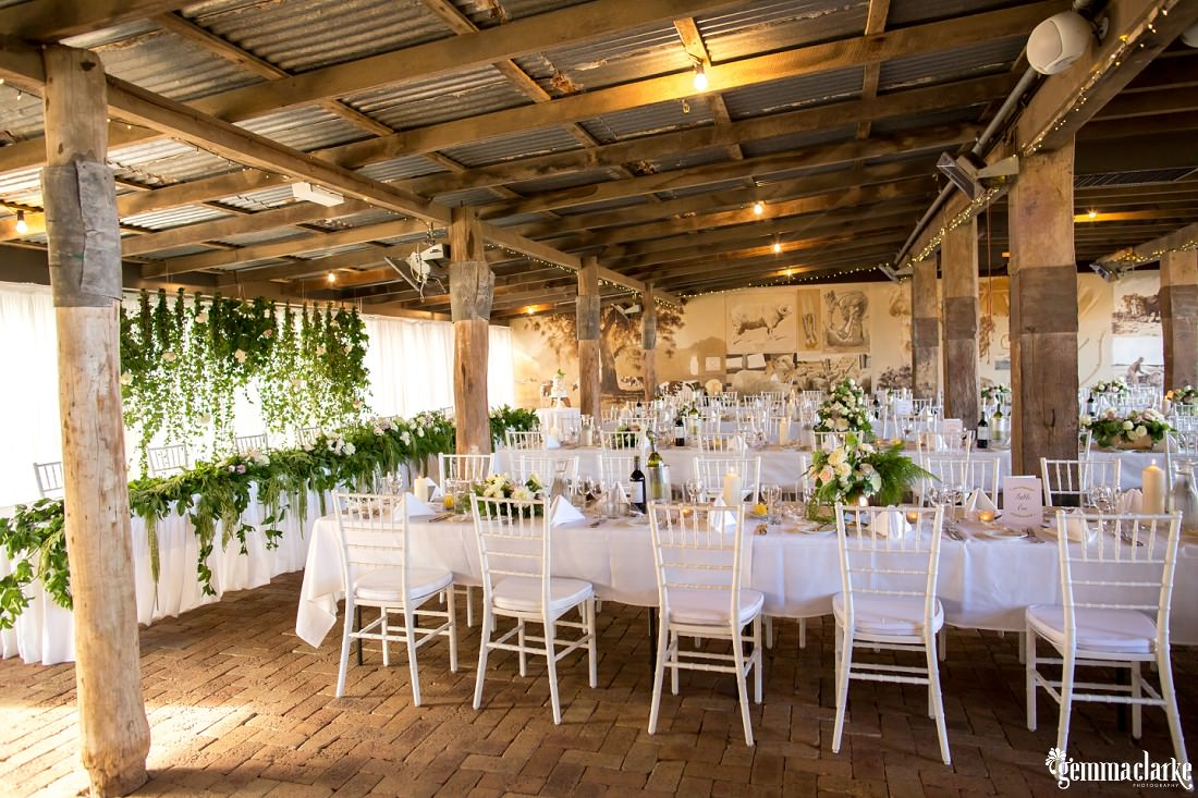 An overall view of tables and chairs at a wedding reception in a wooden farm building