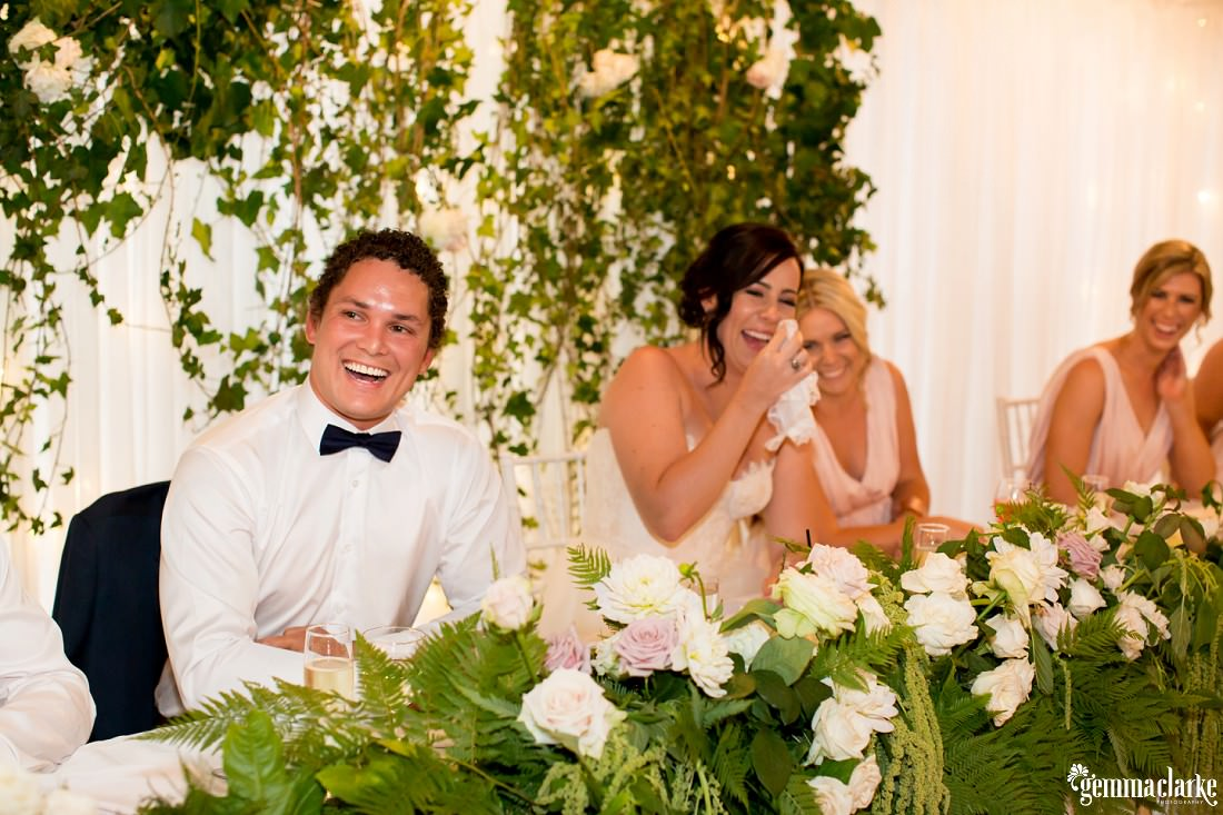 A bride and groom and two bridesmaids laughing at a wedding reception