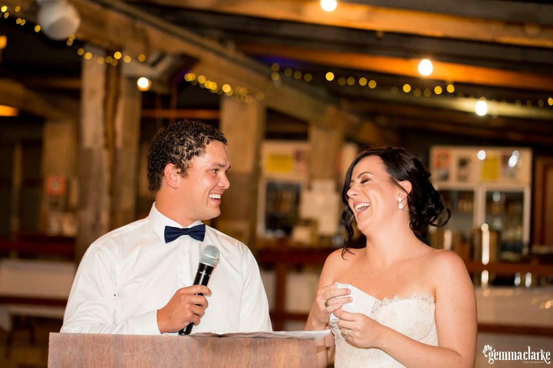 A laughing bride and groom delivering a speech at their wedding reception
